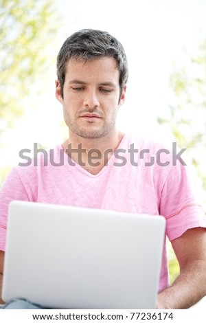 Handsome man with laptop outdoors - stock photo