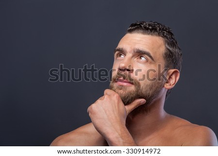 Handsome man with naked shoulders and beard is thinking. He is standing and looking up pensively. The man is touching his chin. Isolated and copy space in left side - stock photo