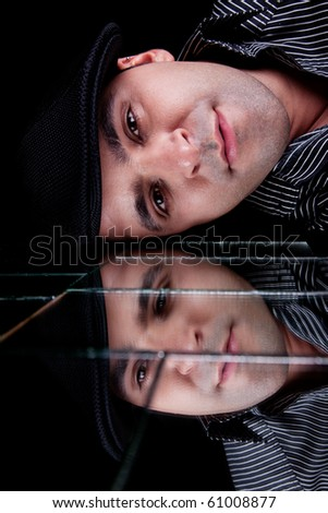 handsome man, with reflexion of the face on the mirror, isolated on back, studio shot - stock photo