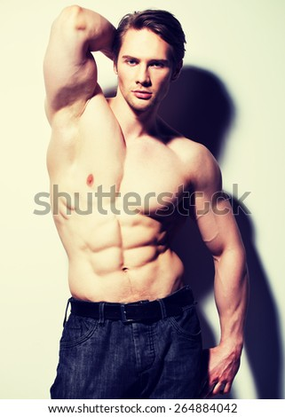 Handsome man with sexy muscular beautiful body posing at studio. - stock photo