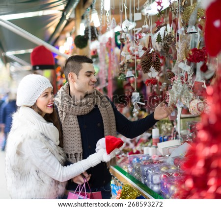 Handsome man with smiling young girlfriend at counter of X-mas market. Shallow focus - stock photo