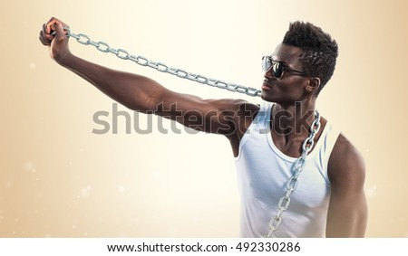 Handsome man with sunglasses and chains over ocher background