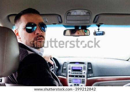 Handsome man with sunglasses is driving in reverse - stock photo