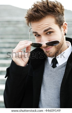Handsome man with sunglasses staring at camera. - stock photo