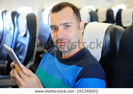 Handsome man with tablet in airplane on his way to vacation - stock photo
