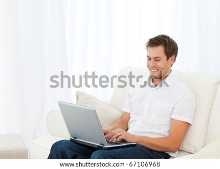 Handsome man working on his laptop while relaxing on the sofa at home - stock photo
