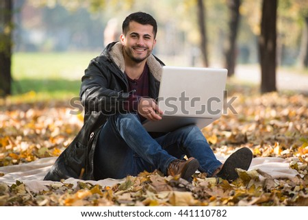 Handsome Man Working On Laptop In Park During Autumn Season - stock photo