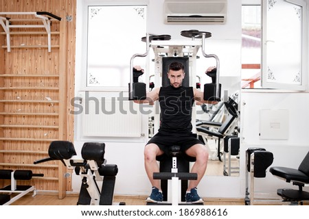 Handsome man working out at gym, daily chest exercise routine. Fitness concept - stock photo