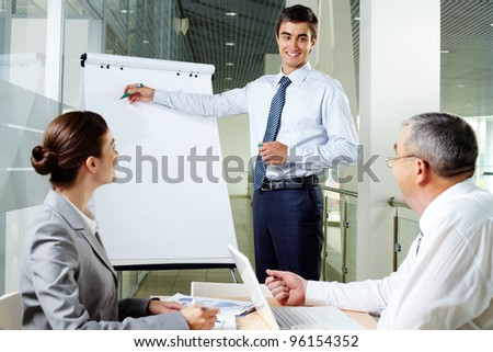 Handsome manager presenting business project to his team