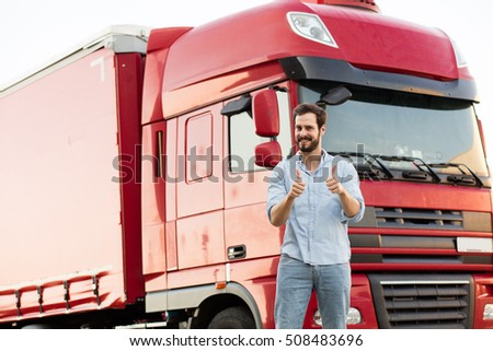 handsome masculine truck driver standing outside with his vehicle behind with pointing the camera