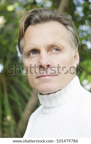 handsome mature blond man in his forties looking pensive - stock photo