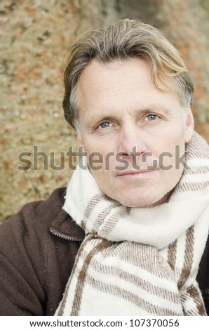 handsome mature blond man in his forties wearing a scarf. - stock photo