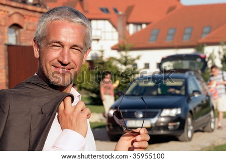 Handsome mature businessman standing in front of house - stock photo