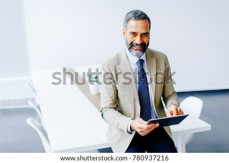 Handsome mature businessman with digital tablet in the office