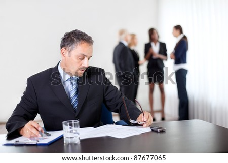 Handsome mature businessman writing on a notepad with his associates in background - stock photo