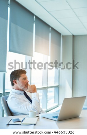 Handsome mature corporate executive in his modern office with sunflare through the large windows, sitting at his desk with his laptop open, looking away and thinking deeply - stock photo