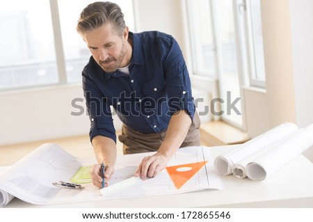 Handsome mature male architect working on blueprint at office desk - stock photo