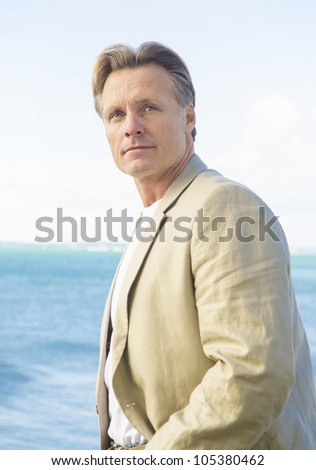 handsome mature man in beige blazer standing by the sea - stock photo