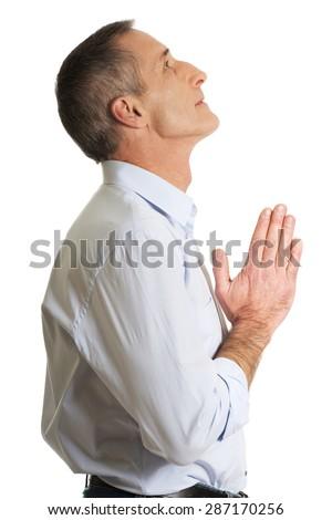 Handsome mature man praying to God. - stock photo