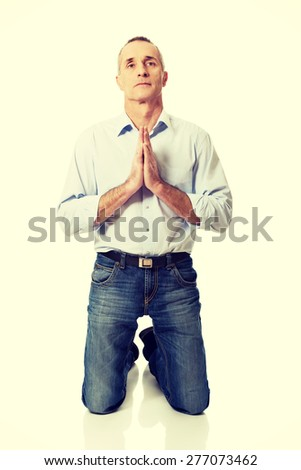 Handsome mature man praying to God on knees. - stock photo