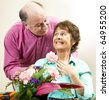 Handsome mature man presents flowers to his beautiful wife. - stock photo