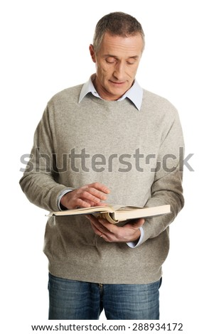 Handsome mature man reading a book.