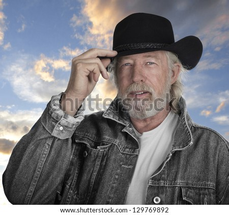 Handsome mature man wearing a gray jeans jacket and black felt cowboy hat with blue eyes with sunset in background - stock photo