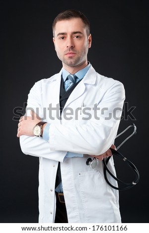 Handsome mature Serious male doctor with stethoscope in hand on black or dark grey background. Classic style in waistcoat with blue shirt and tie - stock photo