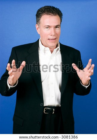 Handsome, mature, white male wearing a black suite and a white shirt gesturing as if telling a joke or story. - stock photo