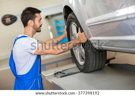 handsome mechanic changing a tire in workshop - stock photo