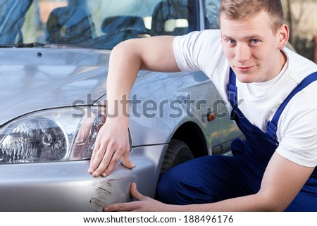 Handsome mechanic during repairing car scratching, horizontal - stock photo