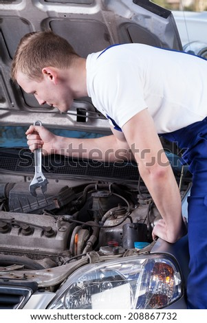 Handsome mechanic with wrench fixing car engine