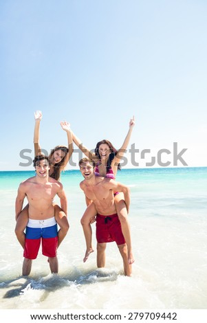 Handsome men giving piggy back to their girlfriends at the beach - stock photo