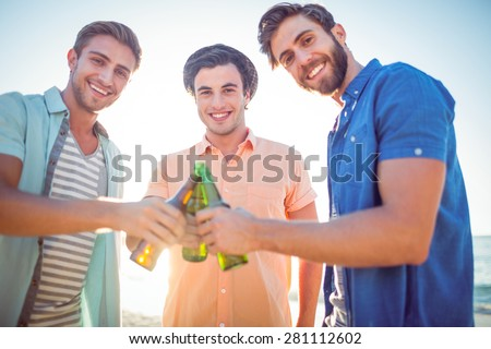 Handsome men toasting at the beach - stock photo