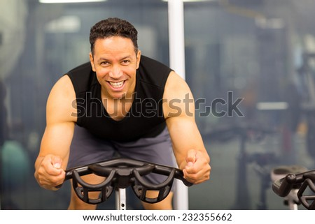 handsome mid age male cyclist on gym bike - stock photo