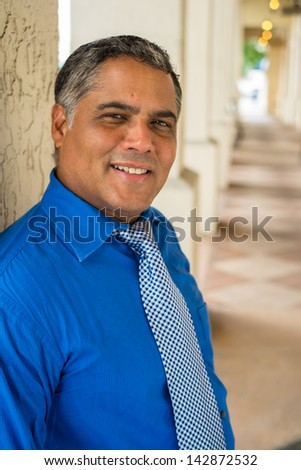 Handsome middle age Hispanic man in an urban setting.