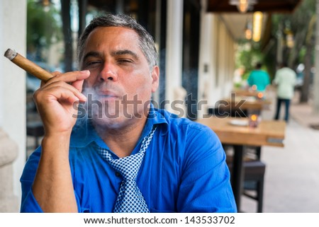Handsome middle age Hispanic man smoking a cigar outdoors in a restaurant. - stock photo