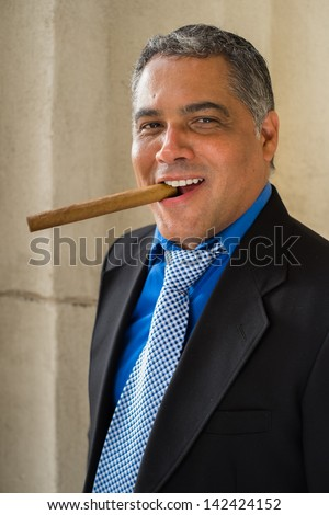 Handsome middle age Hispanic man smoking a cigar outdoors in a urban setting. - stock photo