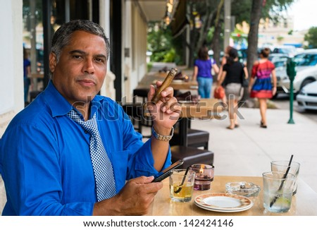 Handsome middle age Hispanic man smoking a cigar while texting outdoors in a restaurant. - stock photo