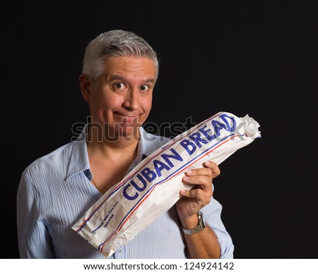 Handsome middle age man  holding a loaf of Cuban bread on a black background.