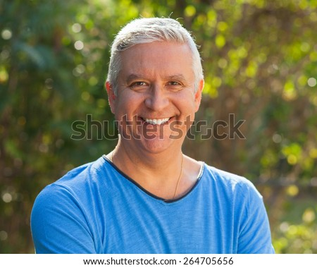Handsome middle age man outdoor portrait with a green background. - stock photo