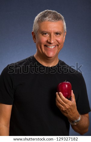 Handsome middle age man with an apple in a studio portrait. - stock photo