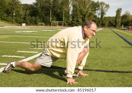 handsome middle age senior man stretching exercising on sports field - stock photo