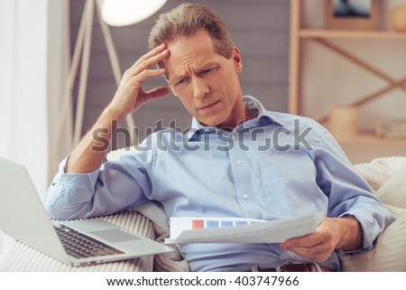 Handsome middle aged businessman in classic shirt is using a laptop and examining documents while working at home - stock photo
