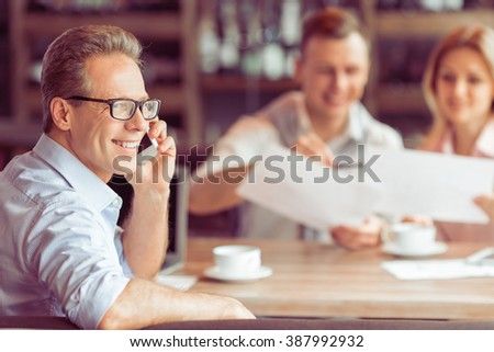 Handsome middle aged businessman in eyeglasses is talking on the mobile phone, in the background young business man and woman working at the restaurant - stock photo