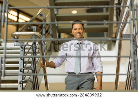 handsome middle aged businessman walking up stairs - stock photo