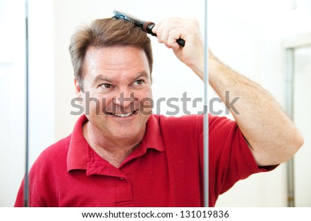 Handsome middle-aged man brushing his hair, looking in the bathroom mirror. - stock photo