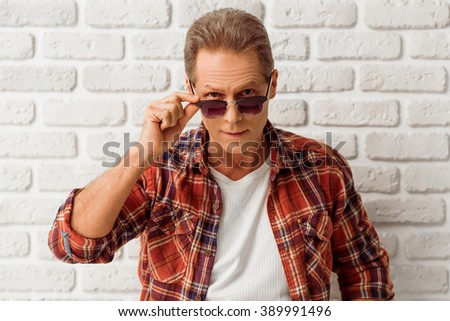 Handsome middle aged man in casual clothes and sunglasses is looking at camera, standing against white brick wall - stock photo