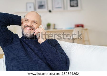 Handsome middle aged man in mustache and beard with hand behind head while looking up in conversation on cell phone indoors - stock photo