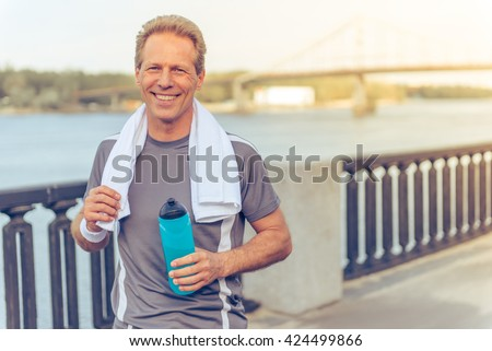 Handsome middle aged man in sports uniform is holding a bottle of water, looking at camera and smiling, resting during morning run - stock photo